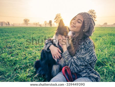 Young beautiful girl stroking her dog in a park at sunset - Asian woman playing with her dog - stock photo