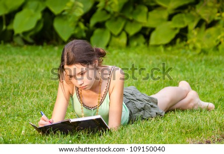 Young beautiful girl studying in the park - stock photo
