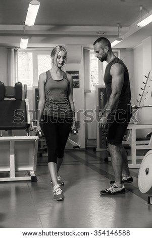 Young beautiful girl takes exercises with a trainer. Training in the gym. Proper exercise. Sport, fitness, lifestyle, gesture and people concept - smiling man and woman doing exercises in gym - stock photo