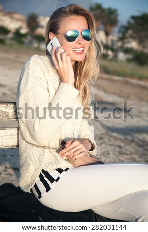 Young beautiful girl talking by mobile phone. Outdoor photo. Sunny day. - stock photo