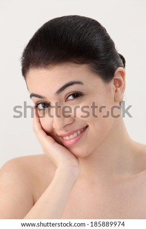 Young beautiful girl touching her face looking at camera