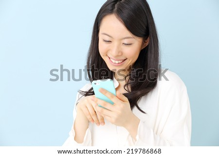 young beautiful girl using mobile phone, against blue background - stock photo