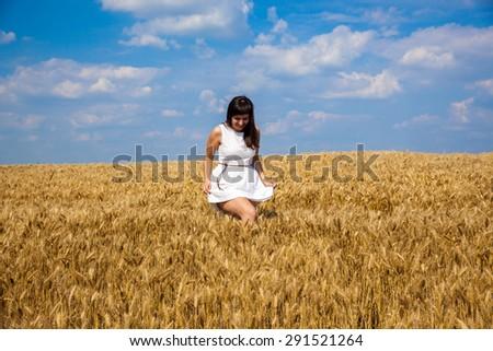 Young beautiful girl walk through golden field of wheat and enjoy life - stock photo