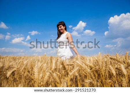 Young beautiful girl walk through golden field of wheat and enjoy life