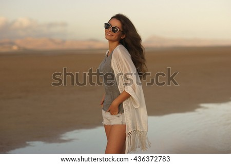 Young beautiful girl walking at the beach at sunset. Woman in gray t-shirt, white cape and shorts posing enjoy sunset