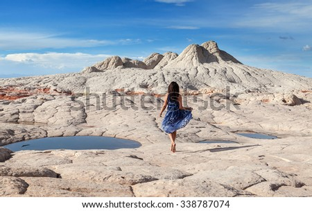 Young beautiful girl walking at White Pocket area of Vermilion Cliffs National Monument - stock photo