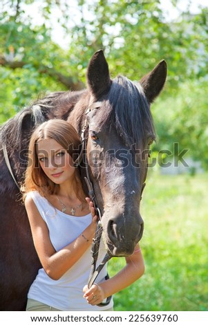 Young beautiful girl walking in the park with a horse - stock photo