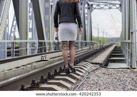 Young beautiful girl walking near railway tracks where the trains run