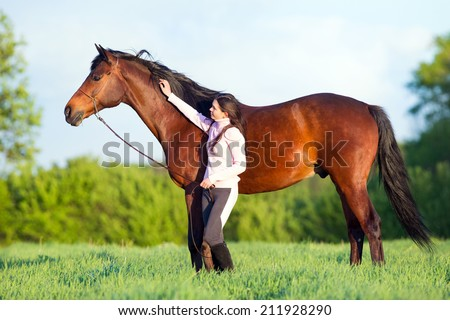 Young beautiful girl walking with a horse in the field - stock photo