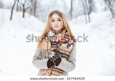 Young beautiful girl walks in winter park on vacation - stock photo