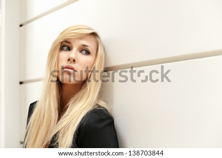 Young beautiful girl wearing formal uniform leaning on the wall looking her left - stock photo