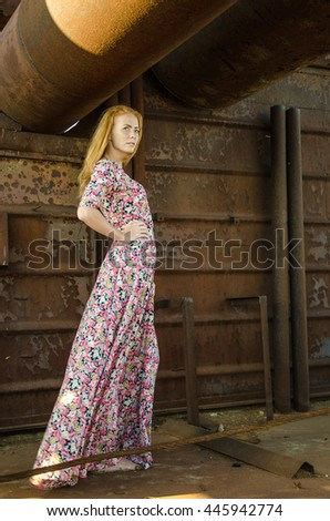 Young beautiful girl wearing long dress on the the background of old ship. Toned.