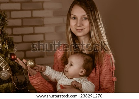 young beautiful girl with a baby near Christmas tree