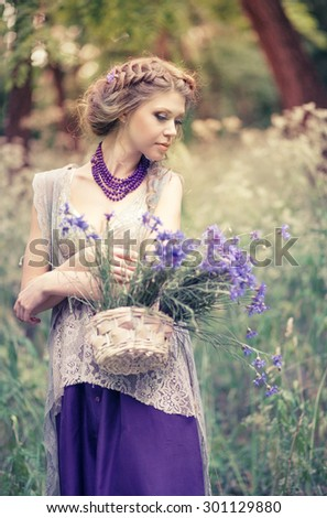 Young beautiful girl with a basket of cornflowers in a charming rustic dress - stock photo