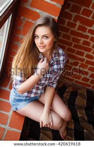 Young beautiful girl with a beautiful smile and long, straight hair standing on the background of a brick wall in a shirt and denim shorts - stock photo