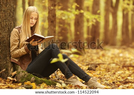 young beautiful girl with a book in the autumn forest - stock photo