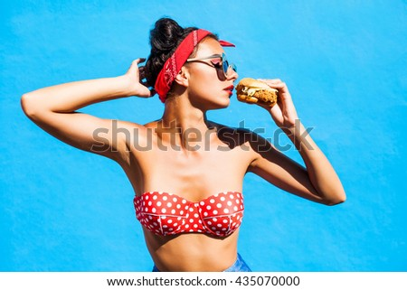 Young beautiful girl with a burger in her hands. Studio. Model. Fast food meal. The concept of food. handsome profile, sunglasses, a bandage on his head, a trendy makeup and hairstyle with horns - stock photo