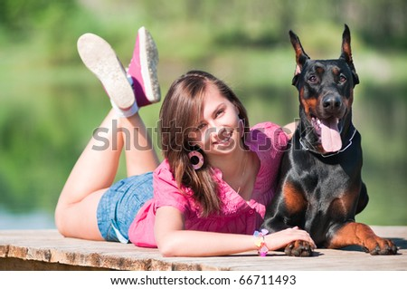 Young beautiful girl with a dog near lake - stock photo