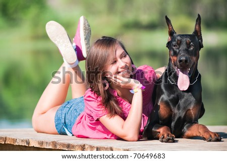 Young beautiful girl with a dog near lake