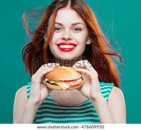 Young beautiful girl with a hamburger satisfied smiles and looks into the camera . Red lips