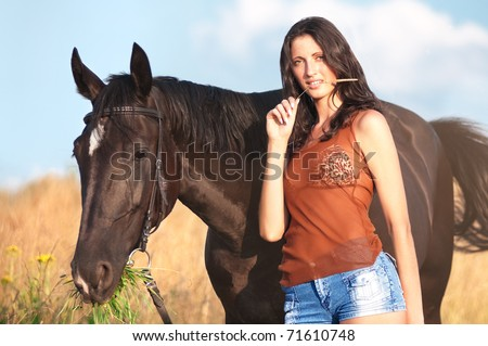 Young beautiful girl with a horse on field