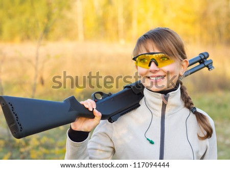 Young beautiful girl with a shotgun in an outdoor - stock photo