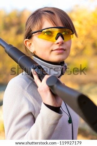 Young beautiful girl with a shotgun in an outdoor
