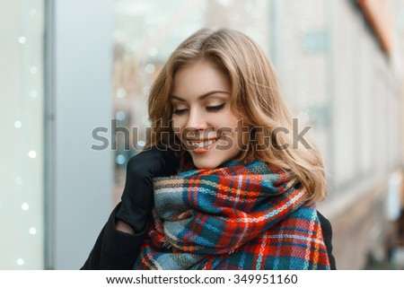 Young beautiful girl with a smile in vintage scarf  and black coat  on the background of shop window