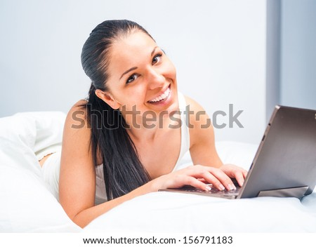 young beautiful girl with a tablet at home in white bed
