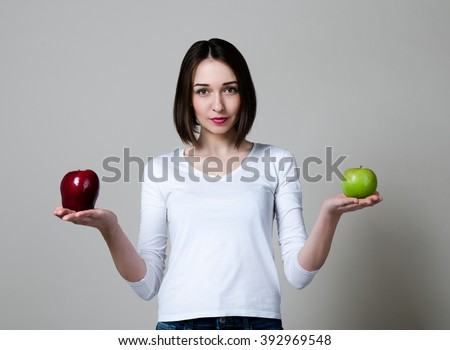 young beautiful girl with Apple in hands on a gray background