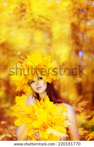 Young beautiful girl with autumn leaves in his hand, and the wreath of autumn maple leaves. Autumn Park in the background. - stock photo