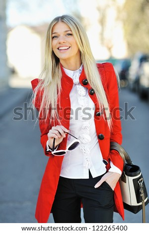 Young beautiful girl with bag and sunglasses in hand - stock photo