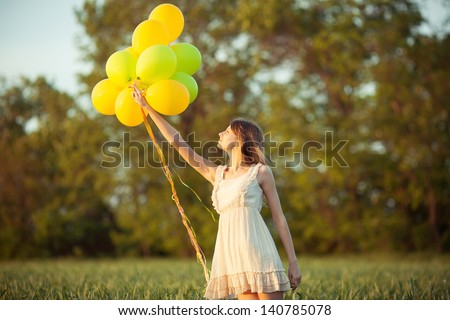 young beautiful girl with baloons in the field - stock photo