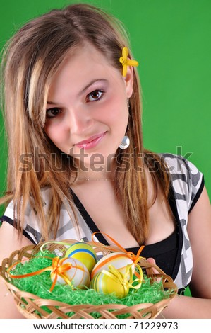 Young beautiful girl with basket and easter eggs in her hand