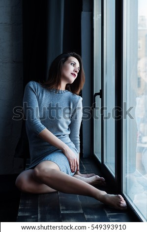 Young beautiful girl with brown hair in a silver dress sitting on the windowsill, leaning against the window. The girl in the profile. Selective focus on face model. Shooting in daylight