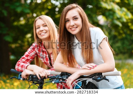 Young beautiful girl with brown hair together with her blond pretty friend standing leaning on the handlebars of their bikes smiling in the green park - stock photo