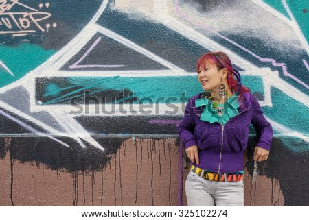 Young beautiful girl with colorful hair and freaky outfit infront of the wall with street art painting