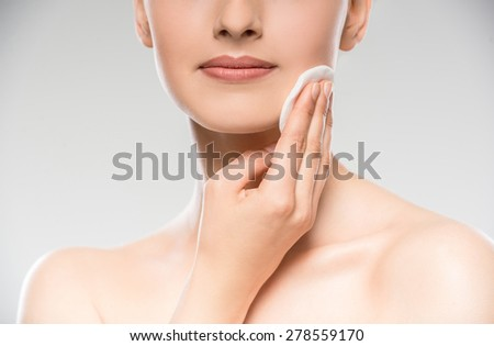 Young beautiful girl with cotton swab cleaning her face. Skin care concept. - stock photo