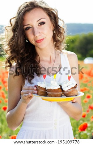 Young beautiful girl with cupcakes in the poppies field