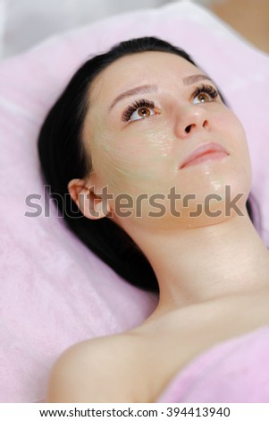 Young beautiful girl with dark hair gets procedure with collagen mask in a beauty salon. Face Skin Care. Cleansing Procedure. Cosmetology. - stock photo