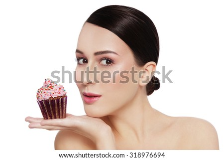 Young beautiful girl with excited expression and tasty cupcake in her hand over white background, copy space - stock photo