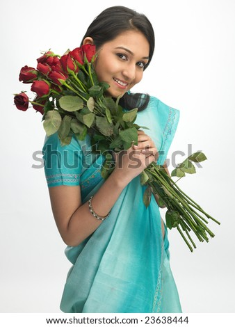 Young beautiful girl with green sari holding red roses - stock photo