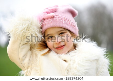 Young beautiful girl with her hand holding her woolly hat while visiting a park during a winter day and wearing a warm coat, smiling outdoors.