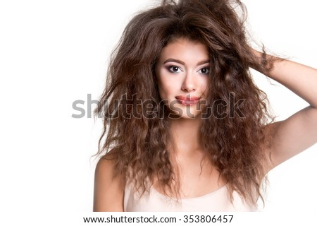 Young beautiful girl with long curly hair. Woman beauty portrait. Unruly hair