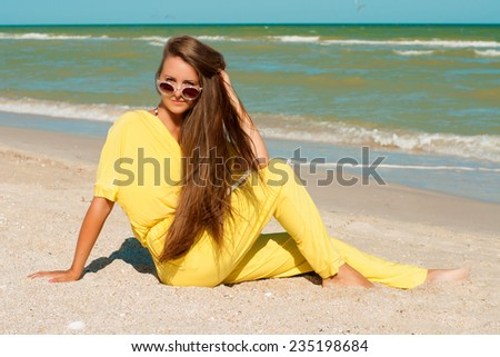 Young beautiful girl with long hair in swimsuit and sunglasses at the beach - stock photo