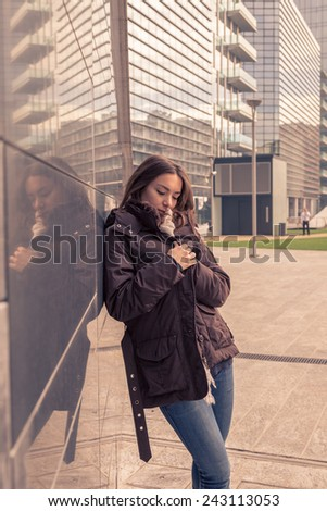 Young beautiful girl with long hair posing in the city streets