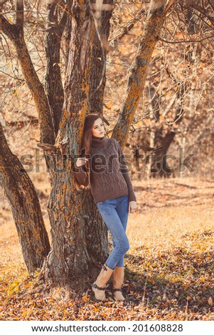 Young beautiful girl with long hair standing in the autumn forest under a tree. Girl wearing a warm sweater, jeans and shoes