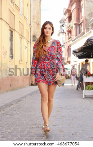 Young beautiful girl with long wavy hair with natural make-up on a city street. Plus size model. Fashion woman in a colorful blue and red suit walking on the city streets.