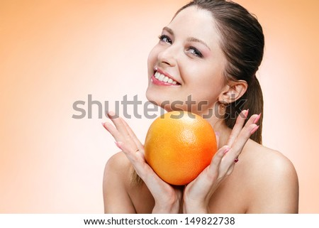 Young beautiful girl with orange / brown-eyed brunette girl holding an orange and smiling - isolated on orange background  - stock photo