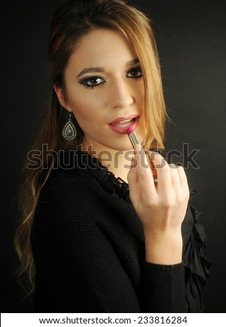 Young beautiful girl with perfect make up putting pink lip stick on her lips - stock photo